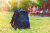 Fototapety Blue school backpack standing on green grass with students in ba