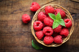 Fresh ripe red raspberries in a wicjer bowl on dark rustic wooden background