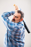 Portrait of angry man who is punching with baseball bat