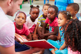Fototapety Volunteer teacher reading to a class of preschool kids