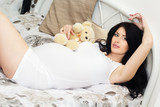 Beautiful pregnant woman is lying on bed