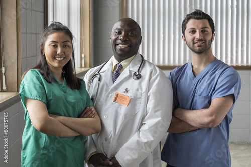 Portrait of a proud Asian female nurse, Caucasian male nurse, and African American doctor