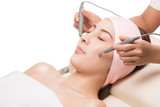 Peaceful brunette getting micro dermabrasion from beauty therapist in the health spa, enjoying a facial massage, isolated on white with clipping path. poster