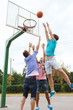 group of happy teenage friends playing basketball
