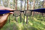 optické brýle v ruce nad rozostřeného pozadí lesa