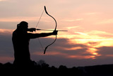 Silhouette archery shoots a bow at a target in sunset sky