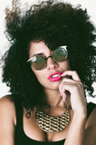 Headshot brunette model with afro like hair, sunglasses, pink lipstick and large golden necklace posing for camera touching lips using left hand