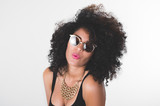 Headshot hispanic model wearing black dress, golden necklace, sunglasses and curly hair making kiss lips for camera