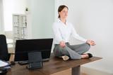 Fototapety Businesswoman Doing Yoga In Office
