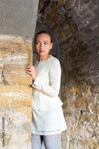 Junge Frau versteckt sich im Kellergewölbe und beobachtet Poster