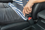 Fototapety Young man fastening seat belt in the car