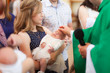 Mother hold baby on ceremony of child christening in church
