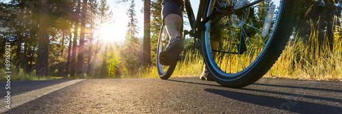 Poster Vélo sur le chemin d'asphalte éclairé par soleil.
