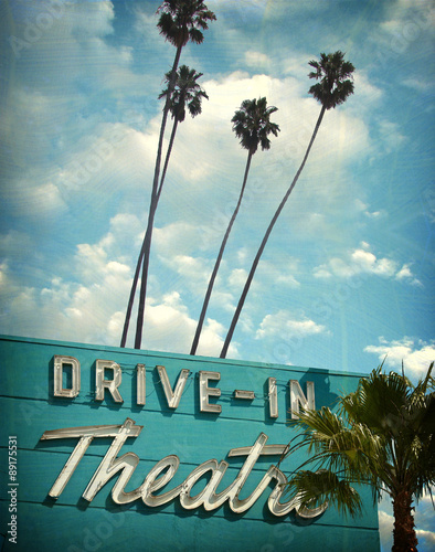 Poster aged and worn vintage photo of neon drive in sign