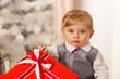 Постер, плакат: Baby boy holds a big red gift box