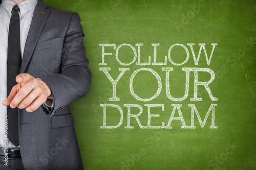 Poster Follow your dream on blackboard with businessman