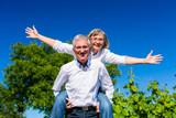 Fototapety Senior Mann trägt Frau auf dem Rücken, sie ist glücklich