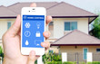 Hand holding white mobile smart phone with smart home applicatio