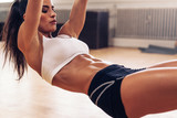 Fototapety Fit young woman exercising at gym