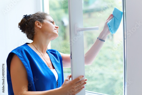 Foto Murales Attractive Woman Washing the Window. Cleaning Company worker wor
