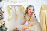Christmas time, adorable girl with lovely curls sitting by the fireplace with stockings