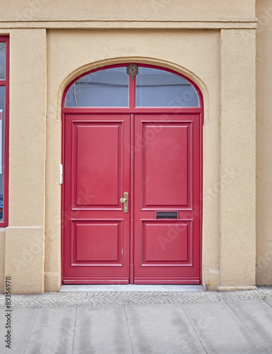 vintage house's vibrant red arched door © Dimitrios