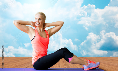 smiling woman doing sit-up on mat over clouds
