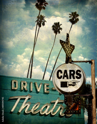 Poster aged and worn vintage photo of drive theater and cars sign with pointing hand