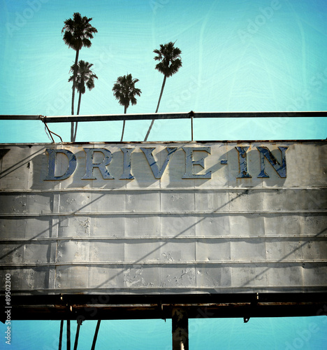 Poster aged and worn vintage photo of retro drive in movie marquee with palm trees