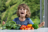 Fototapety Cute little boy sitting at the table excited about vegetable meal, bad or good eating habits, nutrition and healthy eating, showing emotions concept