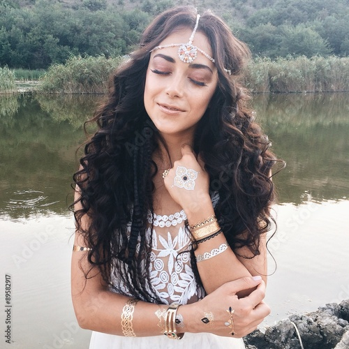 Foto op Aluminium Exclusieve young beautiful woman in a boho style dress posing near lake