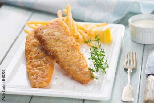 Fotobehang Restaurant Fish and chips. Fried fish fillet with french fries wrapped by p