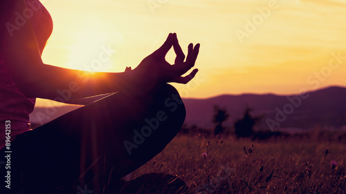 Wall mural Young athletic woman practicing yoga on a meadow at sunset, silhouette
