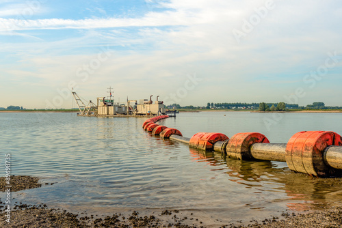 Floating suction dredge in the river Poster