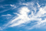 White cirrus clouds against a blue sky background