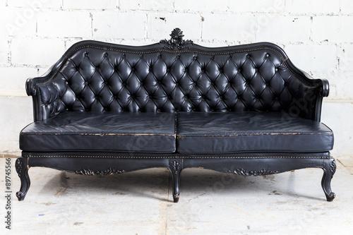 Juliste vintage sofa on white wall.
