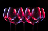 Fototapety Wine glasses lit by red, blue, lilac nightclub party lights on black background