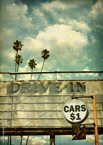Poster aged and worn vintage photo of drive in movies sign with palm trees
