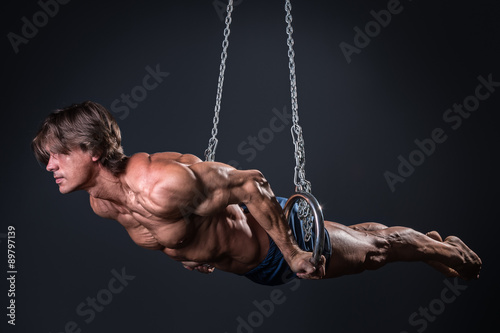 Fototapeta Strong gymnast guy on the rings