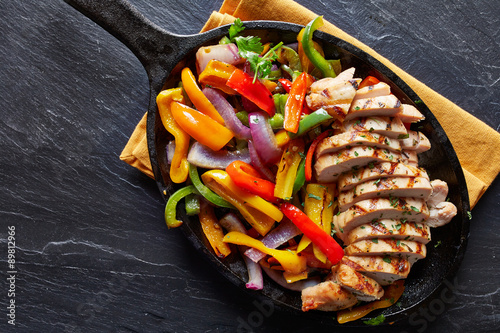 Poster mexican grilled chicken fajitas in iron skillet shot from overhead on slate