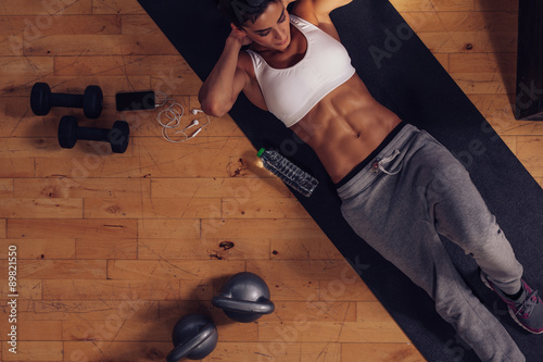 Muscular woman doing abs workout in gym Plakát