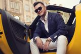Fototapety Stylish man sitting in sport car
