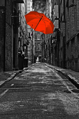 Red umbrella in a dark urban alleyway