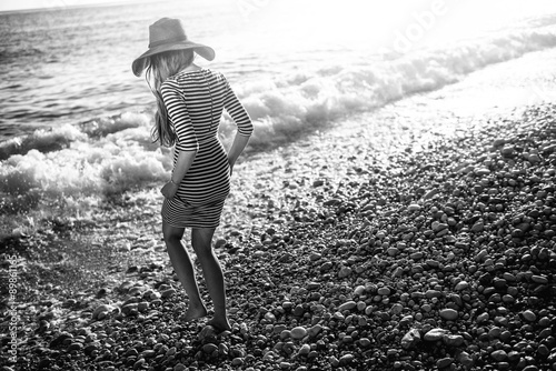 Poster Woman in stripped dress with a hat on the beach