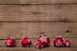 Rote Kugeln auf Holz Hintergrund als Dekoration zu Weihnachten.
