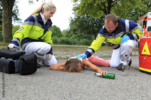Foto Murales Junge Frau betrunken am Boden mit Sanitäter