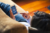 Woman shopping by mobile phone laying at home. Blue screen. She is laying on the sofa.