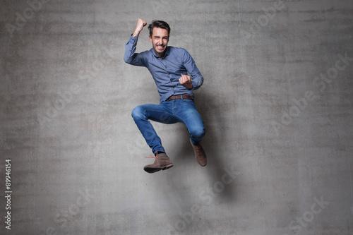euphoric business man jump wall