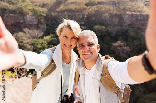 Poster hiking couple taking selfie together
