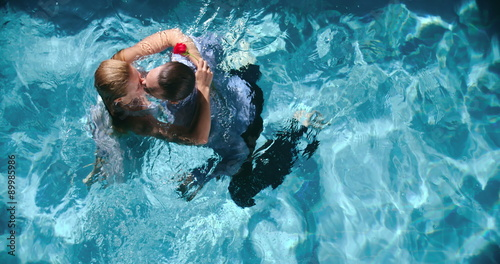 Beautiful Young Couple In Evening Clothes Kissing Passionately In Swimming Pool